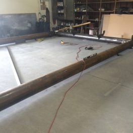 large steel canopy laid out in shop